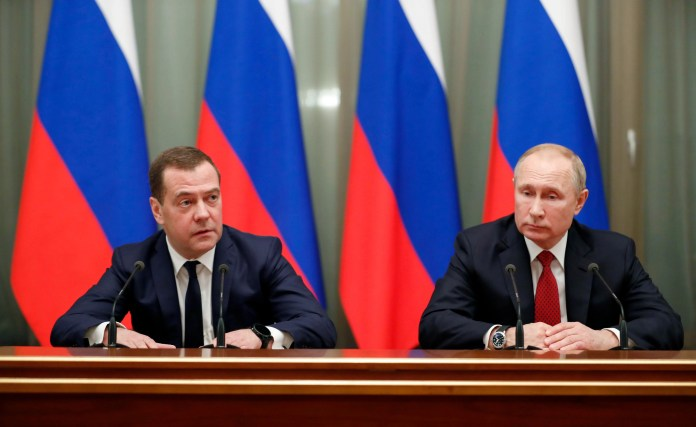 Russian President Vladimir Putin on the right and Prime Minister Dmitry Medvedev meet with members of the government in Moscow on January 15, 2020.