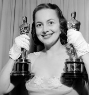 Olivia de Havilland holds up her two trophies after winning a second best actress Oscar in 1950 for her performance in