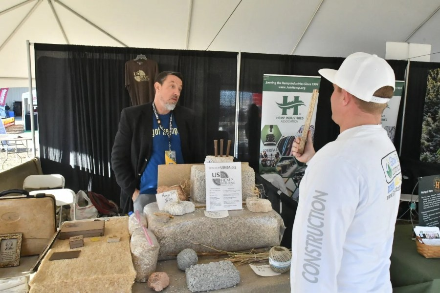 Chad Sanden holds a hemp board, twice as strong as oak wood, at the Hemp Building Association booth at the 2020 World Ag Expo.