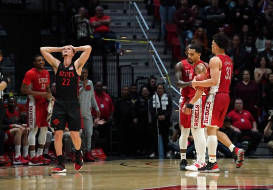 San Diego State Aztecs guard Malachi Flynn (22) reacts in the second half as UNLV Rebels guard Amauri Hardy (3) and guard Elijah Mitrou-Long (55) and guard Marvin Coleman (31) look on the second half at Viejas Arena. UNLV won 66-63.