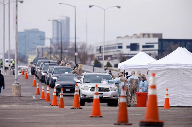 Cars line up for a drive through testing center for the COVID-19 coronavirus at the Denver Coliseum on Mar 14, 2020.