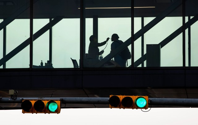 A hospital worker checks the temperature of a coworker at a pedestrian walkway at Dell Seton Medical Center at the University of Texas on March 25, 2020, where almost all visitors have been prohibited amid the coronavirus outbreak.