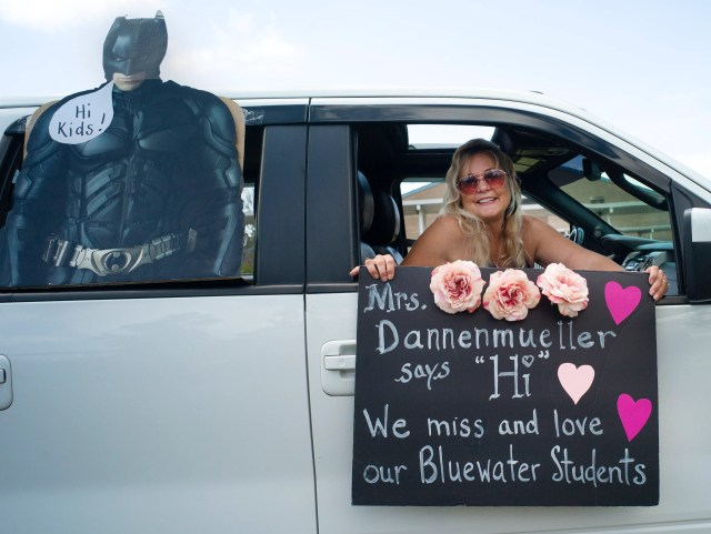 """Teacher Julie Dannenmueller holds her sign for the students with the help of the Caped Crusader as teachers from Bluewater Elementary school have a parade through their school's neighborhoods to sat """"hi"""" to their homebound students on March 27, 2020 in Niceville, FL."""
