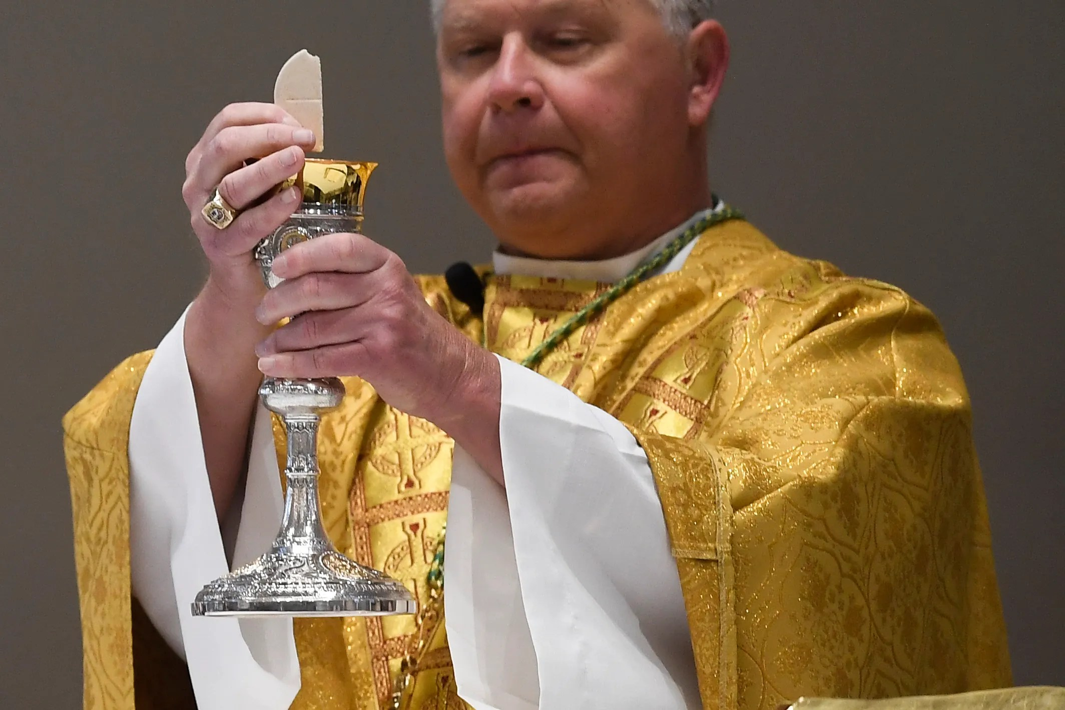 Knoxville Catholic Bishop Richard Stika holds Easter mass at the Cathedral of the Most Sacred Heart of Jesus in Knoxville, Tennessee, on April 12, 2020. Pews were empty due to coronavirus restrictions. A live stream of the service was offered on the church's website.