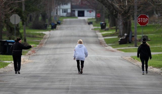 This trio finds ample room to walk through a Rochester, N.Y. neighborhood on April 14, 2020 while following social distancing protocols during the coronavirus pandemic.