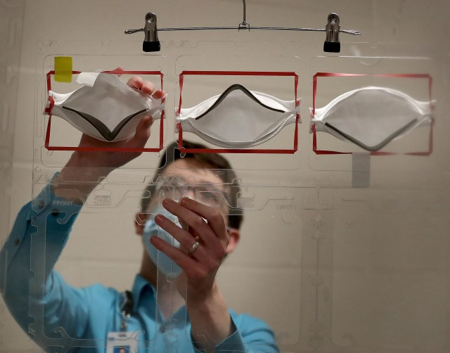 As masks became harder to get, hospitals began looking for ways to re-use them. Dan Cates demonstrates how used N95 masks will be placed onto plastic racks to be sterilized by a robot utilizing ultraviolet light at Regions Hospital in St. Paul, Minn.
