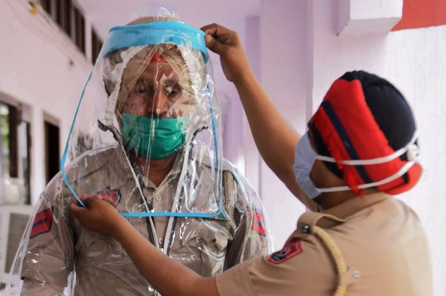 Police personnel try Personal Protective Equipment (PPE) during a government-imposed nationwide lockdown as a preventive measure against the COVID-19 coronavirus, in Amritsar on April 16, 2020.