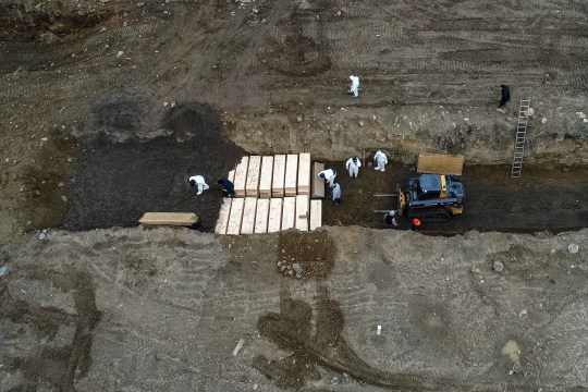 Workers wearing personal protective equipment bury bodies in a trench on Hart Island in New York's Bronx neighborhood. A disproportionate number of coronavirus deaths in New York have struck the city's Latin American community.