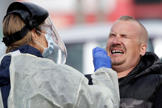 A man reacts as a medical staffer tests shoppers who volunteered at a pop-up community COVID-19 testing station at a supermarket carpark in Christchurch, New Zealand, April 17, 2020. New Zealand is into week four of a 28-day lockdown in a bid to stop the spread of the new coronavirus.