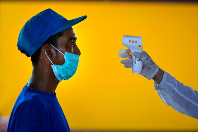A resident living close to a boarding house, which housed foreign students from Malaysia, gets his temperature taken by an Indonesian health officer amid the COVID-19 coronavirus pandemic in Banda Aceh, Indonesia on April 20, 2020.