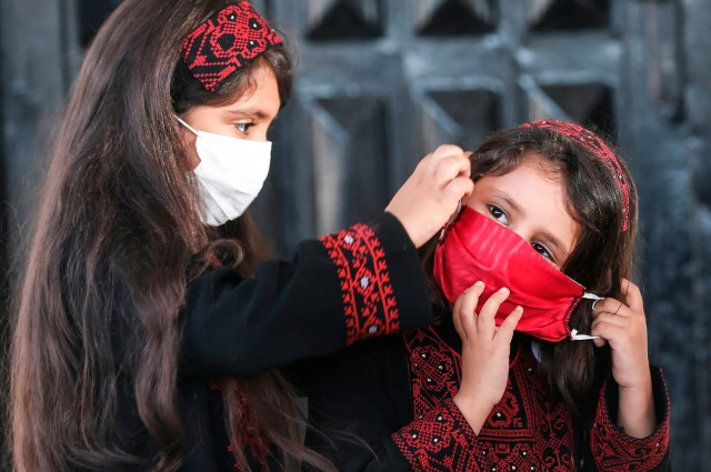 Palestinian girls wearing protective masks attend a graduation ceremony from the Police Academy amid concerns about the spread of the coronavirus COVID-19 in Gaza City on May 7, 2020.