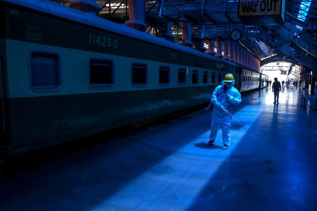 A worker wearing protective gear sprays disinfectant at the Lahore railway station during a government-imposed nationwide lockdown as a preventive measure against the COVID-19 coronavirus, in Lahore on May 7, 2020.