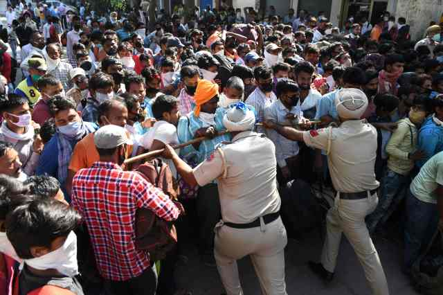 Policemen push back stranded migrant workers as they gather for a medical screening before taking a train to Sultanpur in Uttar Pradesh state to return to their hometowns after the government eased a nationwide lockdown imposed as a preventive measure against the COVID-19 coronavirus, in Amritsar on May 20, 2020.