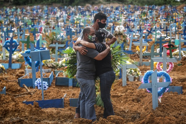 Relatives of a deceased person mourn during a mass burial of coronavirus (COVID-19) pandemic victims at the Parque Taruma cemetery on May 19, 2020 in Manaus, Brazil. Brazil has over 260,000 confirmed cases and more than 17,000 deaths caused by coronavirus (COVID-19) pandemic.
