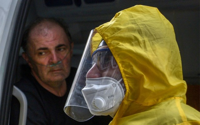 A doctor wearing a face mask and protective gear stands next to an ambulance at the Grigor Lusavorich Medical Centre in Yerevan on May 29, 2020, amid the COVID-19 outbreak, caused by the novel coronavirus.