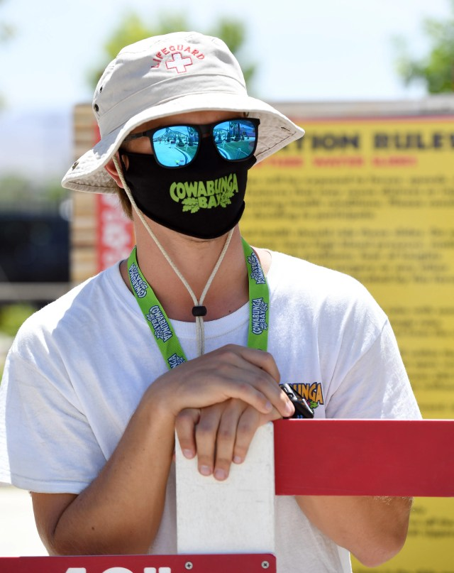 Lifeguard Mark Rerecich wears a mask as he watches over guests at Cowabunga Bay Water Park, which was allowed to open for the first time this weekend because of the coronavirus (COVID-19) pandemic on May 30, 2020 in Henderson, Nevada.