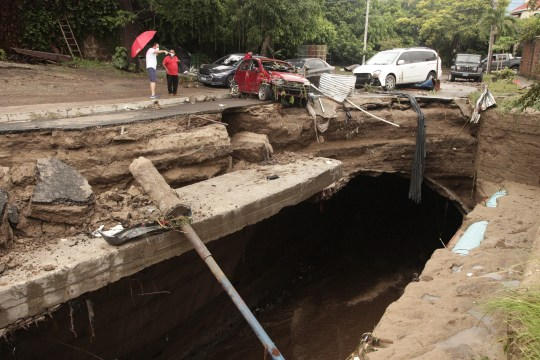 Locals look at the damage after the Acelhuete River flooded in San Salvador, El Salvador, killing at least 17 people.