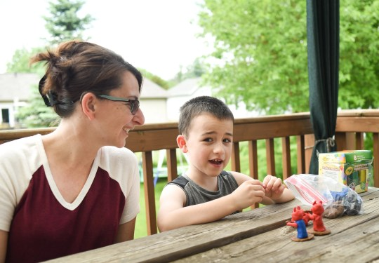 Rebecca Urban and son Aiden, 7, play outdoors on Thursday, June 4, 2020, on the patio of Urban's home in Holt. Urban, a mother of two and a paraprofessional for the Holt school district, has profound hearing loss in both ears.