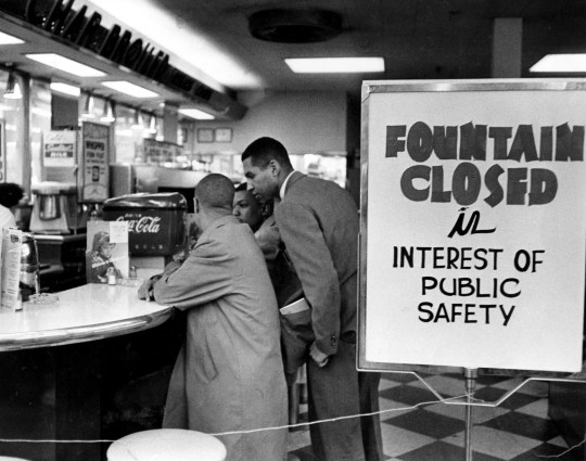 In this 1960 photo, student sit-in leader Rodney Powell, standing, talks with two of his companions after the lunch counter at a downtown Nashville Walgreen's Drug Store, which was closed by its owner when the sit-ins started. Protesters were aiming to desegregate such locales, and eventually succeeded as the nation's attention was drawn to their struggle.  (Via OlyDrop)
