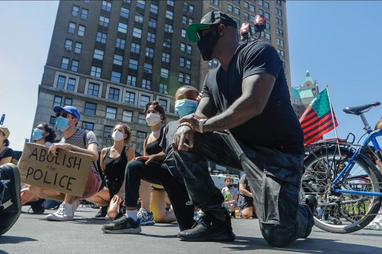 Protesters take a knee at Borough Hall as part of a solidarity rally calling for justice over the death of George Floyd, and to highlight police brutality nationwide, Tuesday, June 9, 2020, in the Brooklyn borough of New York.