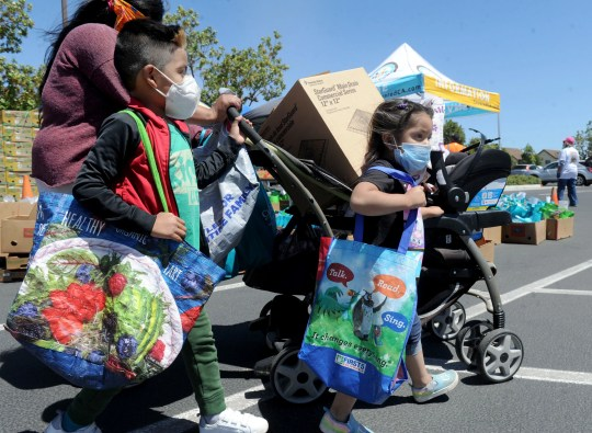 Gilberto Gonzalez, 6, left, and his sister Viviana Gonzalez, 4, help their mother Rosalba Gonzalez carry food at the Feeding The Frontline event at Our Lady of Guadalupe in Oxnard on Saturday, June 13, 2020.