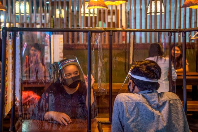 Young people sit in a restaurant with plastic dividers to apply social distancing rules amid concerns for the COVID-19 coronavirus at a shopping mall in Surabaya, East Java on June 16, 2020.