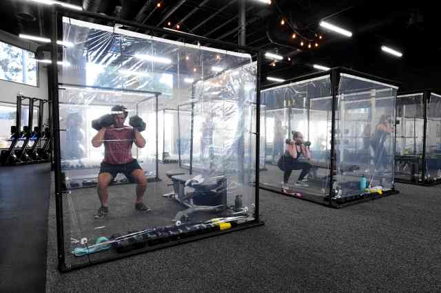 People exercise at Inspire South Bay Fitness behind plastic sheets in their workout pods while observing social distancing on June 15, 2020 in Redondo Beach, Calif. as the gym reopens today under California's coronavirus Phase 3 reopening guidelines.