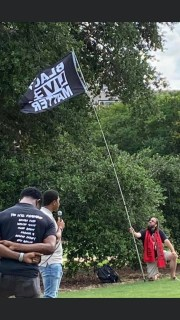 Charleston music teacher and activist Aaron Comstock flies a Black Lives Matter flag at a recent protest.