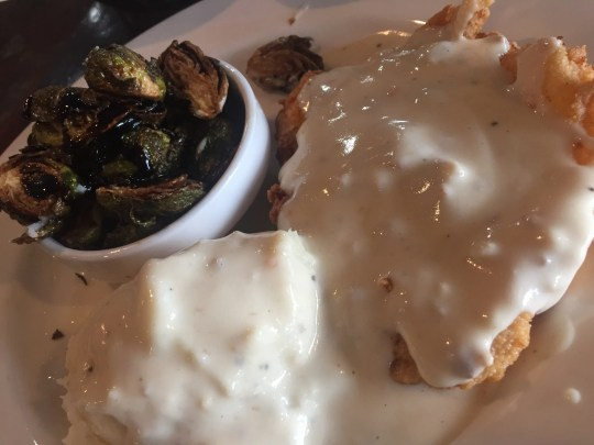 Emma's Southern Kitchen's chicken-fried chicken -- a fried breast piece topped with white sausage gravy, mashed potatoes and a side of okra.