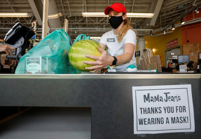 Aubrey Prugger bags groceries for a customer while wearing a face covering at MaMa Jean's Natural Market on Republic Road in Springfield, Illinois to slow the spread of COVID-19 on Friday, July 10, 2020.