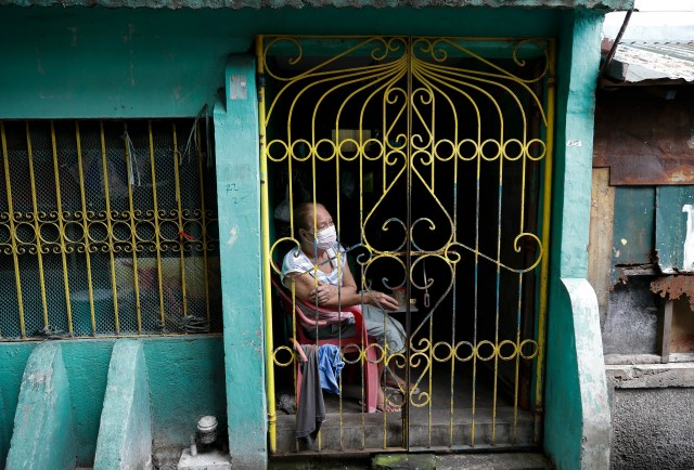 A resident sits inside her home during the start of a lockdown due to a rise in COVID cases in the city of Navotas, Manila, Philippines, Thursday, July 16, 2020.
