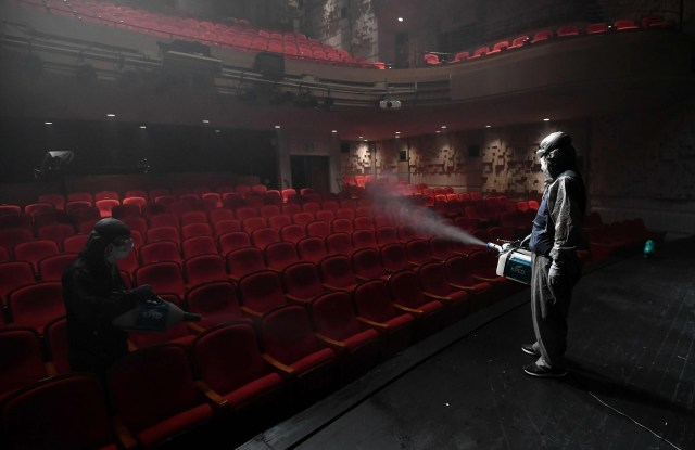 A South Korean worker wearing protective clothes sprays disinfectant in a theatre at Sejong Center in Seoul on July 21, 2020, amid the COVID-19 coronavirus pandemic.