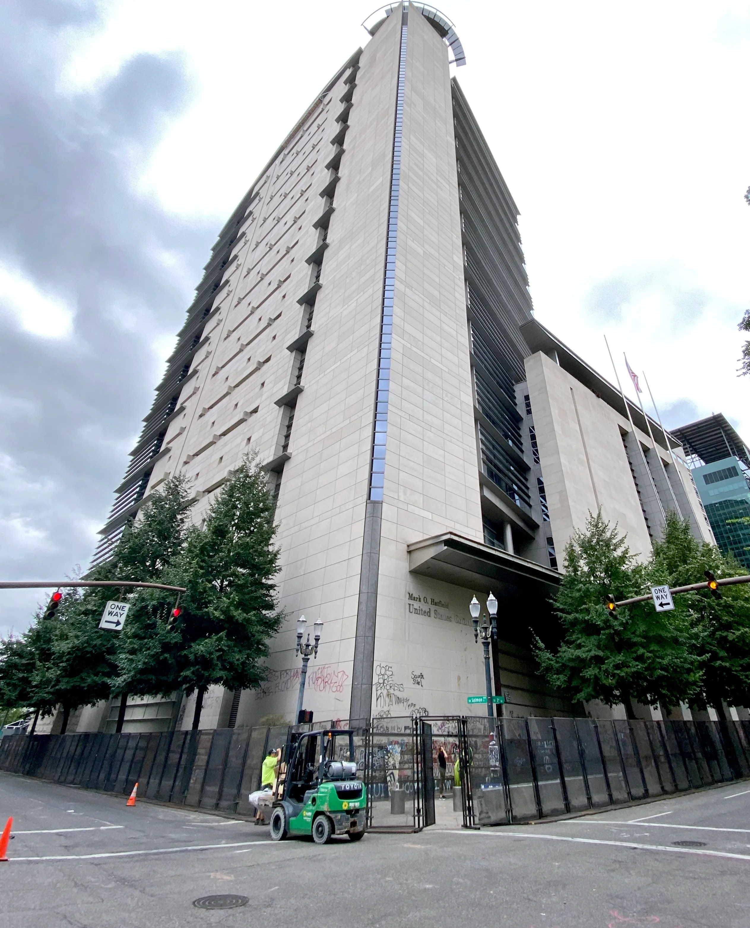 Workers erect metal fencing and concrete barriers around the federal courthouse in Portland, Ore., on July 22.