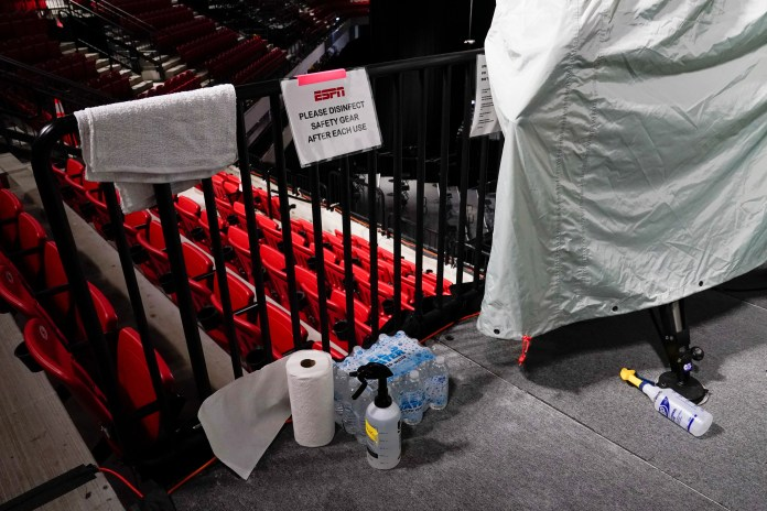July 29: Disinfectant spray sits near television cameras inside one of the arenas.