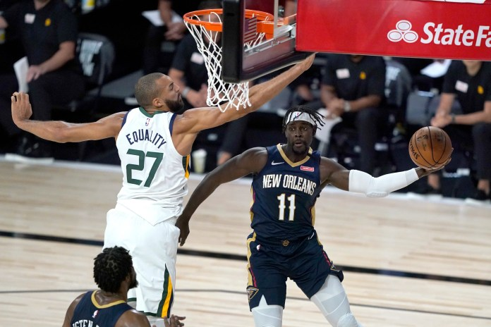 July 30: Pelicans guard Jrue Holiday (11) tries to pass around Jazz center Rudy Gobert (27) during the first game of the NBA's resumed season.