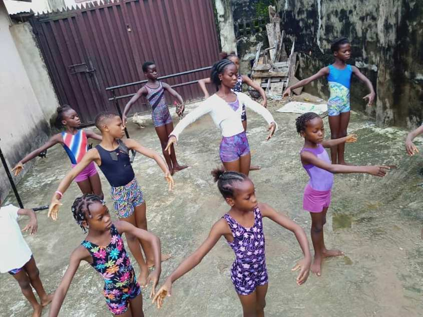 A group of students from Lagos, Nigeria's Leap of Dance Academy gathers to take class on a concrete-covered space outside their teacher's home, which doubles as the dance studio.