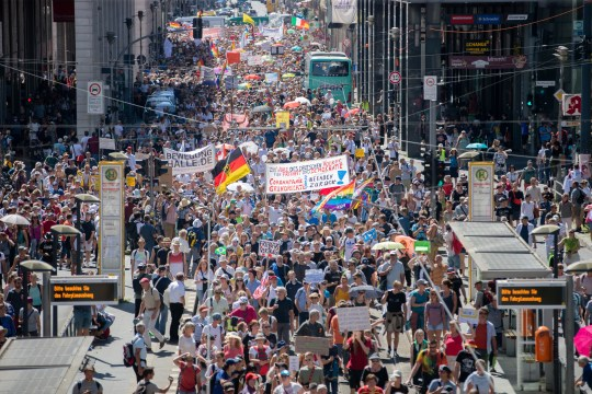 "Thousands march along the 'Friedrichstrasse' during the demonstration against corona measures in Berlin, Germany, Saturday, Aug. 1, 2020. The initiative ""Querdenken 711"" has called for this. The motto of the demonstration is ""The end of the pandemic - Freedom Day."""