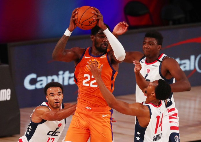 July 31: Suns center Deandre Ayton (22) grabs a rebound between a trio of Wizards defenders.