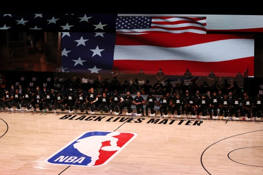 Players, coaches and staff kneel during the national anthem before the game between the Rockets and the Mavericks on Friday.
