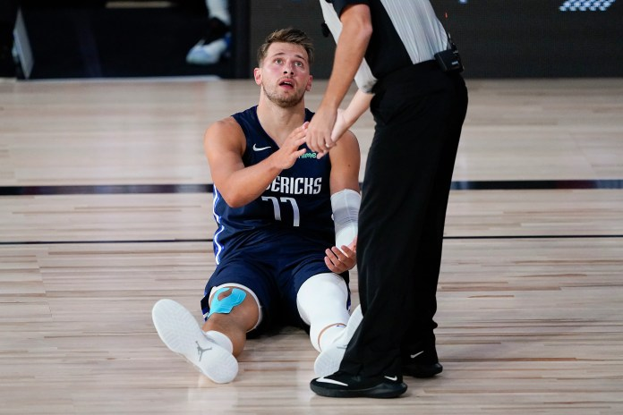 Aug. 2: Mavericks guard Luka Doncic gets a hand from an official after hitting the deck against the Suns.