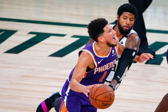 Phoenix Suns' Devin Booker (1) draws a foul from Los Angeles Clippers' Paul George (13) during an NBA basketball game Tuesday, Aug. 4, 2020, in Lake Buena Vista, Fla. (Kevin C. Cox/Pool Photo via AP)