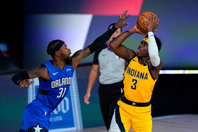 Aug. 4: The Indiana Pacers' Aaron Holiday shoots over the Orlando Magic's Terrence Ross during the Pacers' 120-109 win.