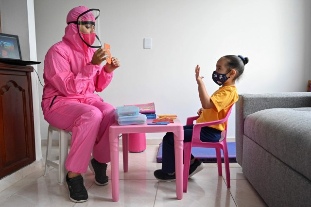 A teacher wearing personal protective equipment as a preventive measure against the spread of the novel coronavirus, COVID-19, gives a class to a girl at home in Cali, Colombia, on Aug. 4, 2020. The