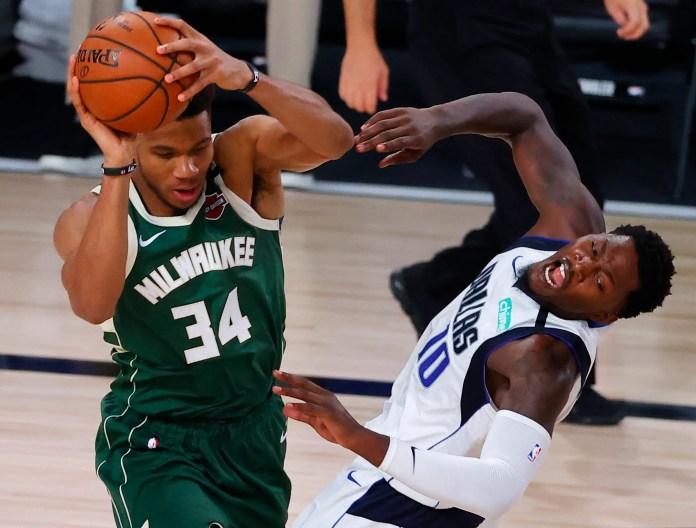 Aug. 8: Bucks forward Giannis Antetokounmpo collides with Mavericks defender Dorian Finney-Smith.