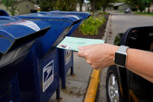 A person drops applications for mail-in-ballots into a mail box in Omaha, Neb., on Aug. 18, 2020. U.S. Postal Service warnings that it can't guarantee ballots sent by mail will arrive on time have put a spotlight on the narrow timeframes most states allow to request and return those ballots.