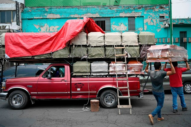 Workers unload coffins from a truck outside a funeral home located in front of the General Hospital in Mexico City on August 20, 2020 amid the COVID-19 coronavirus pandemic.