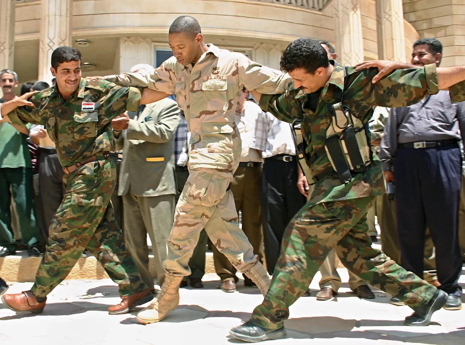 Then Col. Dana JH Pittard, US army commander for the Iraqi Dyala province, dances with national guardsmen during an Iraqi flag raising ceremony in Baquba, northeast of Baghdad, July 6, 2004.