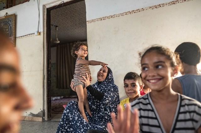 Suad Al-Dairi plays with her grandson in their house during a coronavirus lockdown in the Al-Karamah neighborhood on September 02, 2020 in Gaza City, Gaza.
