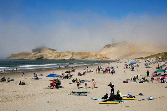 People scatter along the beach on Sunday in Pacific City, Oregon. Crowds were sparse in the morning but continued to grow throughout the day.
