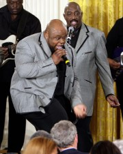 Bruce Williamson, center, and Otis Williams, right, of The Temptations perform for President George W. Bush, seated, center back to camera, at a celebration of African American History Month, Tuesday, Feb. 12, 2008, in the East Room of the White House in Washington.